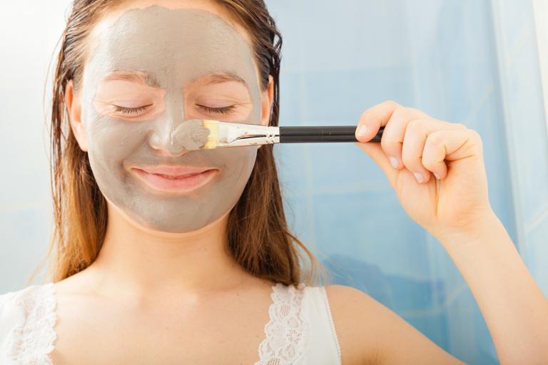 a teenage girl applying a gray mud facial mask